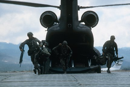 Military men stepping out of a helicopter