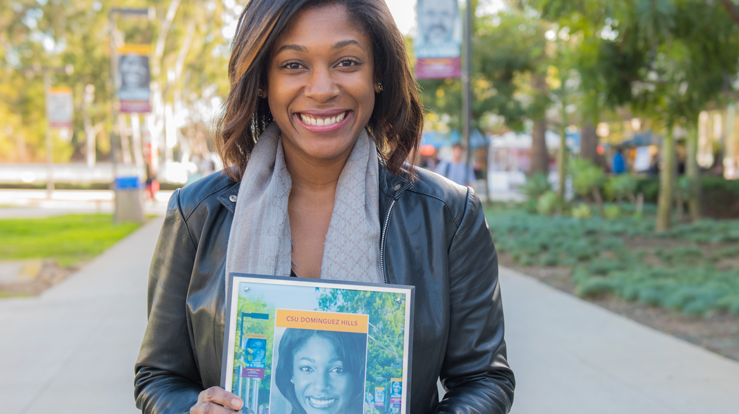 Photo of CSUDH Alumn Markette Sheppard on campus holding her 'I'm a Toro' plaque