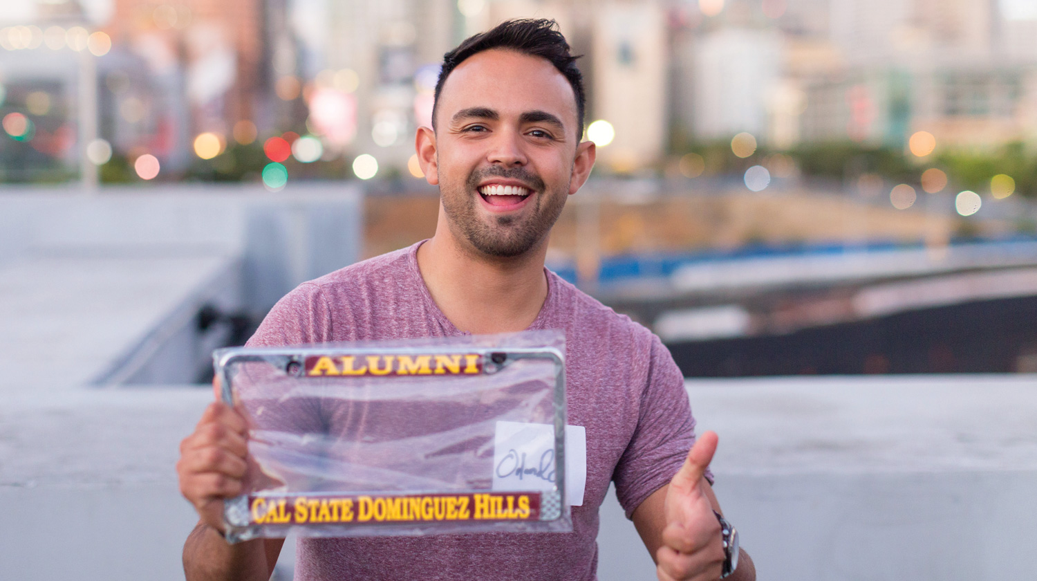 male alumn at a previous CSUDH alumni event holds CSUDH license plate gift