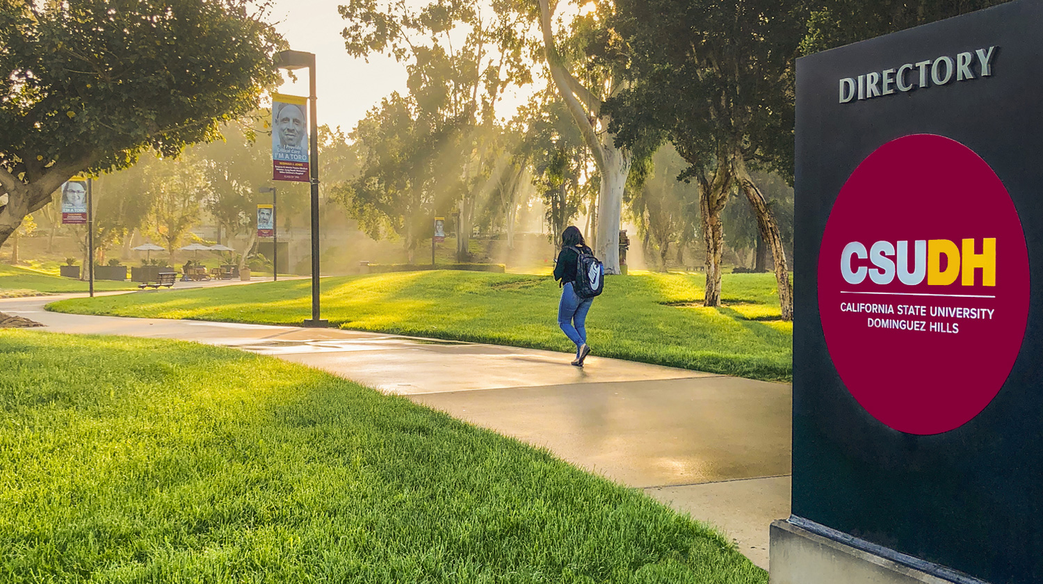photo of campus directory signage with logo, student walking along pathway