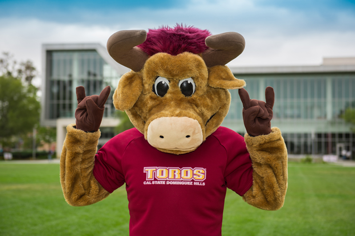 photography sample - Teddy the Toro mascot make the toro hand sign outside Loker Student Union