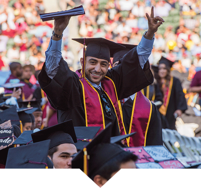 a student in cap and gown raising his hand