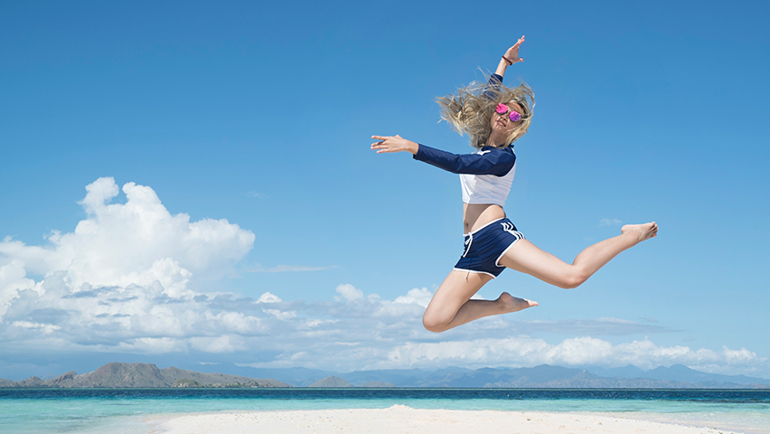 Happy girl jumping above sandy beach