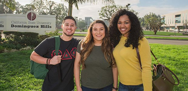 Photo of students posing in front of CSUDH entrance
