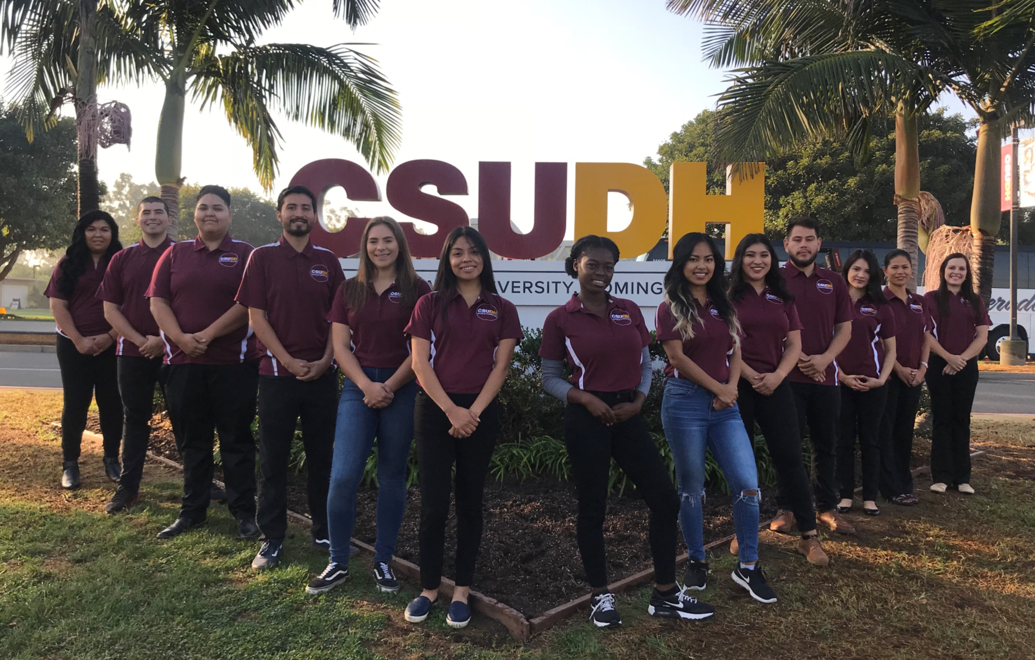 A picture of all staff members who work in the Office of Student Life standing in front of the large CSUDH sign on Victoria Street.