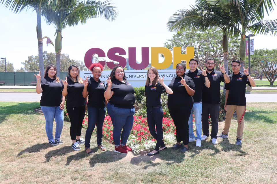 Transfer Peer Academic Coaches standing in front of CSUDH signage